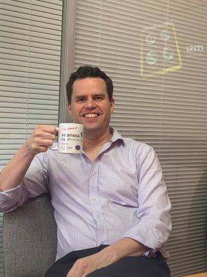 Ben Wheeler celebrating with his Swansea Digital Marketing mug