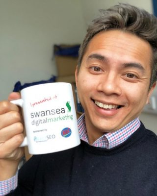 Kenon Man celebrating with his Swansea Digital Marketing mug