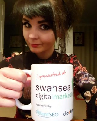 Natalie Holborow celebrating with her Swansea Digital Marketing mug